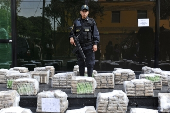 A police officer stands amid packages of cocaine seized along with other materials in anti-drug operations in Peru, during a presentation to the press in Lima on May 18, 2012. More than 1.5 tons of cocaine were confiscated.