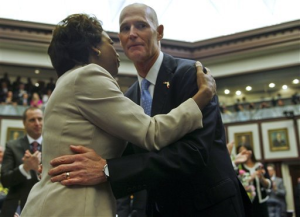 In this Tuesday, March 5, 2013 file photo, Florida Lt. Gov. Jennifer Carroll and Gov. Rick Scott embrace prior to his State of the State speech in the Florida House of Representatives in Tallahassee, Fla. Carroll resigned and nearly 60 other people were charged in a widening scandal of a purported veterans charity that authorities said Wednesday, March 13, 2013 was a $300 million front for illegal gambling.