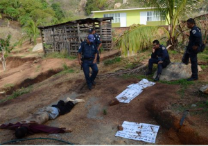 Police wait for forensic workers after two people were slain inside a primary school, prior to the arrival of students, in the Pacific resort city of Acapulco, Mexico, Mayo 30, 2012. Several messages from a drug gang were left next to the bodie